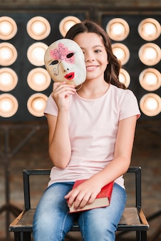Uśmiechnięta dziewczyna trzyma venetian maskę w jej rękach