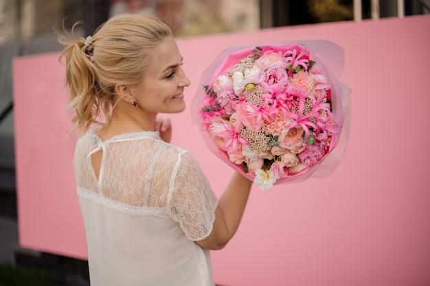 Uśmiechnięta dziewczyna trzyma wiosna bukiet delikatni różowi i biali kwiaty