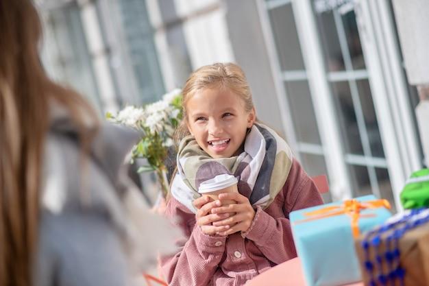 Uśmiechnięta dziewczyna trzymająca filiżankę kawy