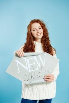 """Uśmiechnięta dziewczyna trzymająca transparent """"nowa kolekcja"""""""