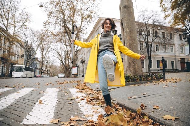 Uśmiechnięta dziewczyna ubrana w płaszcz i kalosze