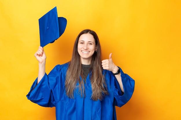 Uśmiechnięta dziewczyna ubrana w szatę ukończenia szkoły pokazuje kciuk w górę, trzymając czapkę.