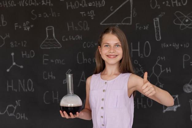 Uśmiechnięta dziewczyna uczy się więcej o chemii w klasie