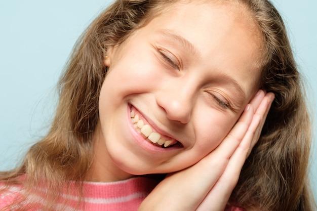 Uśmiechnięta dziewczyna udając, że śpi, używając rąk jako poduszki. emocjonalny wyraz twarzy.