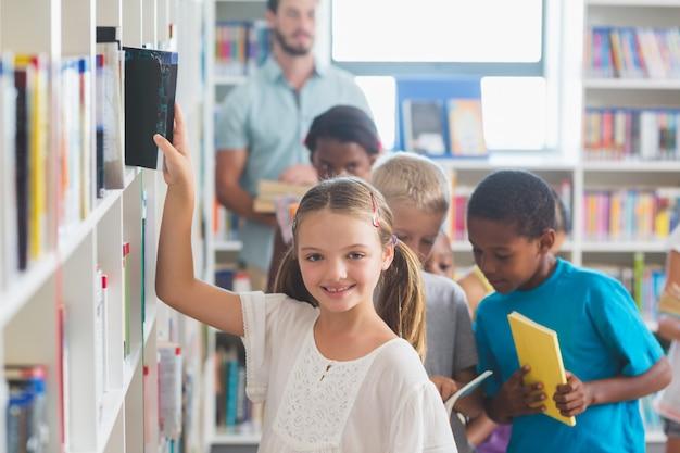 Uśmiechnięta dziewczyna usuwa książkę z półka na książki w bibliotece