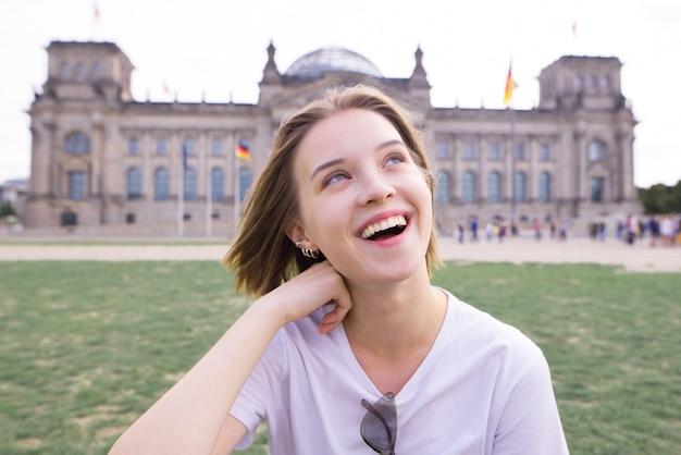 Uśmiechnięta dziewczyna w białej koszulce na tle architektury