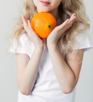 Uśmiechnięta dziewczyna w białej koszulce trzymając pomarańczę w dłoniach. zdjęcie pionowe