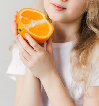 Uśmiechnięta dziewczyna w białej koszulce trzymając w rękach pół pomarańczy. zdjęcie pionowe
