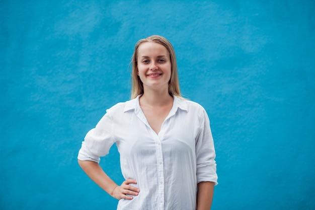 Uśmiechnięta dziewczyna w białej koszuli na niebieskiej ścianie