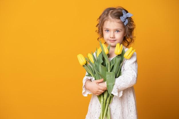 Uśmiechnięta dziewczyna w białej sukni na żółtym tle. wesoły szczęśliwe dziecko z bukietem kwiatów tulipanów.