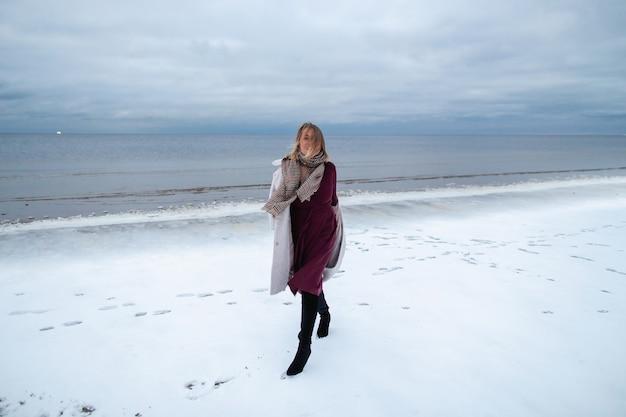 Uśmiechnięta dziewczyna w bordowej sukience i płaszczu na tle zimowego morza. portret kobiety na morzu, śnieg, wietrzna pogoda, zimny obraz atmosferyczny.