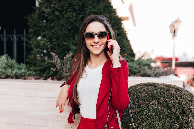 Uśmiechnięta dziewczyna w ciemnych okularach przeciwsłonecznych rozmawia przez telefon podczas pozowania w pobliżu zielonego krzewu