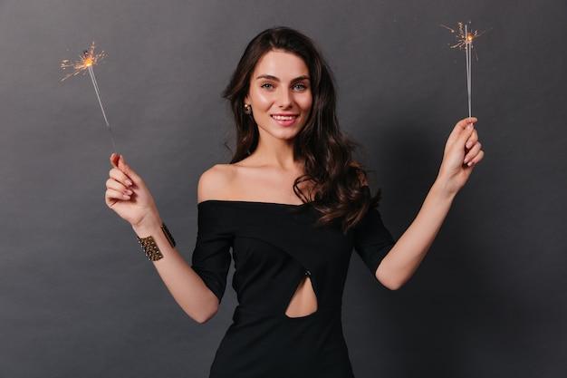 Uśmiechnięta dziewczyna w czarnej sukni patrzy na kamerę i trzyma zimne ognie na ciemnym tle.