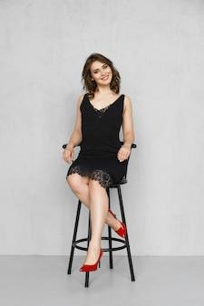 Uśmiechnięta dziewczyna w czarnej sukni z koronkowym brzegiem i paskami siedzi na krześle w studio