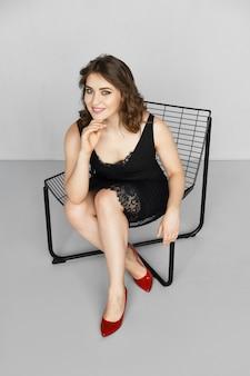 Uśmiechnięta dziewczyna w czarnej sukni z koronkowym brzegiem i paskami siedzi na krześle