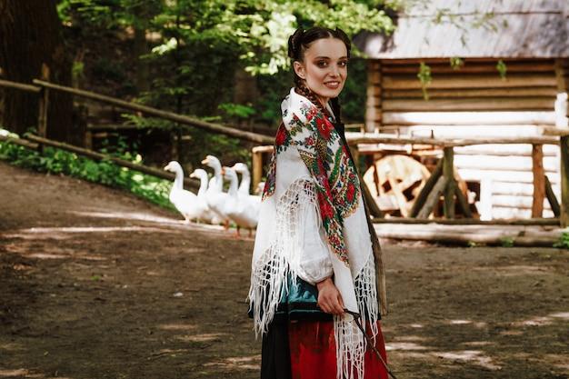 Uśmiechnięta dziewczyna w haftowanej ukraińskiej sukience chodzi po podwórku