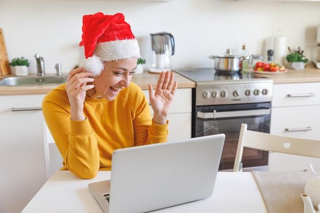 Uśmiechnięta dziewczyna w kapeluszu santa macha ręką, rozmawiając wideo z rodziną przez kamerę internetową
