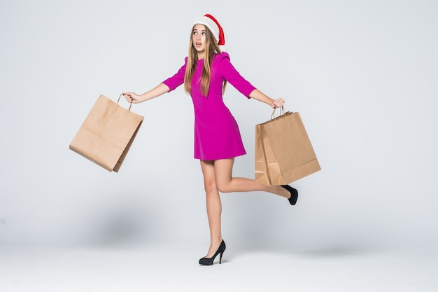 Uśmiechnięta dziewczyna w krótkiej różowej sukience i obcasie nowy rok kapelusz trzymać papierowe torby na zakupy na białym tle