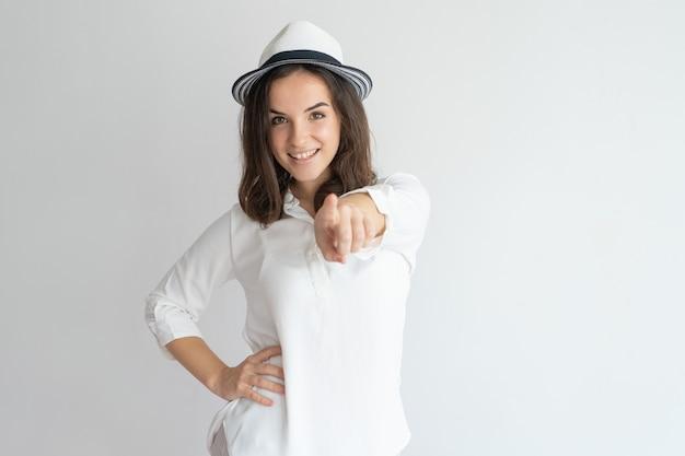 Uśmiechnięta dziewczyna w lato kapeluszu wybiera ciebie.