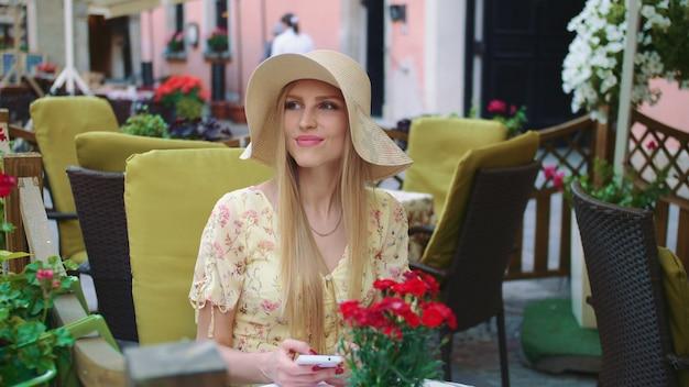Uśmiechnięta dziewczyna w na zewnątrz restauracji. rozochocony młodej kobiety obsiadanie przy stołem w outside restauraci na wygodnej ulicie.