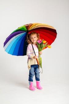 Uśmiechnięta dziewczyna w pasującej różowej koszula i podeszczowych butach trzyma tęcza parasol na białym tle