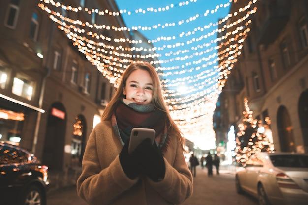 Uśmiechnięta dziewczyna w płaszczu i smartfonie w dłoniach stoi na tle dekoracji ulicznych