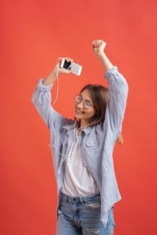 Uśmiechnięta dziewczyna w przypadkowych ubraniach i słuchawkach tanczy ruchome ręki.