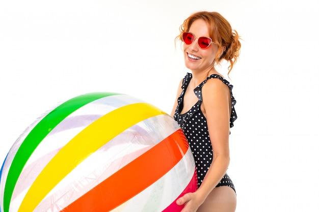 Uśmiechnięta dziewczyna w retro swimsuit i okularach przeciwsłonecznych trzyma pasiastą piłkę na białej ścianie