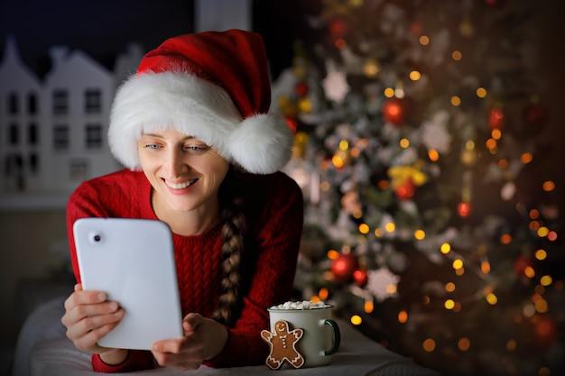 Uśmiechnięta dziewczyna w swetrze i czapce mikołaja komunikuje się przez telefon w świąteczną noc