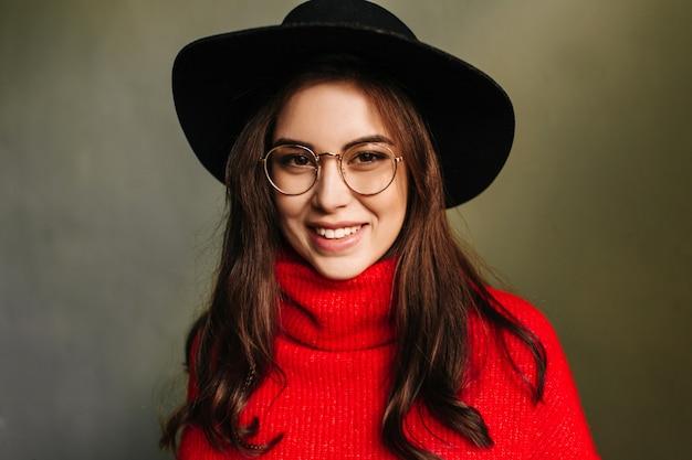 Uśmiechnięta dziewczyna w świetnym nastroju. ujęcie modelu z brązowymi oczami w jasny sweter z dzianiny i kapelusz na szarej ścianie.