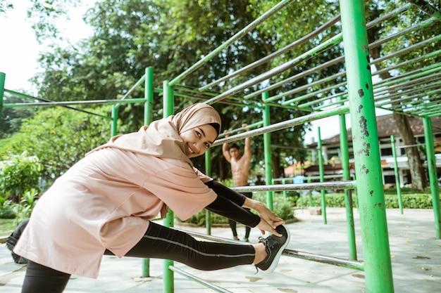 Uśmiechnięta dziewczyna w welonie rozciąga nogę na żelaznym pręcie, zanim zacznie ćwiczyć, aby schudnąć