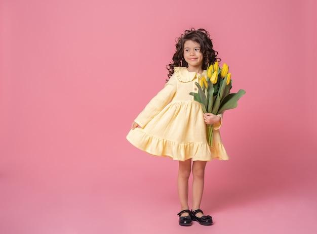 Uśmiechnięta dziewczyna w żółtej sukience na różowym tle studio
