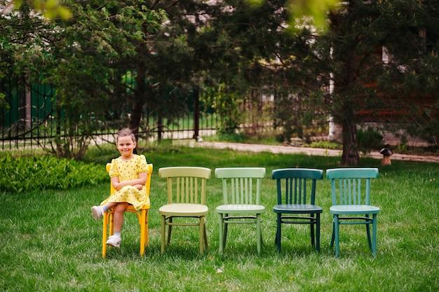 Uśmiechnięta dziewczyna w żółtej sukience siedzi ze skrzyżowanymi nogami na wiedeńskich kolorowych krzesłach, stojąc w linii