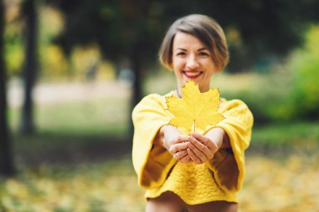 Uśmiechnięta dziewczyna w żółtym swetrze jesienią trzyma w rękach liść klonu.