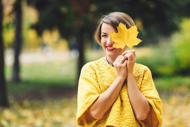 Uśmiechnięta dziewczyna w żółtym swetrze w parku jesienią zamyka oko z liściem klonu.