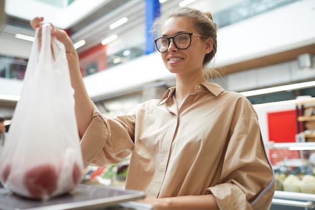 Uśmiechnięta dziewczyna waży pomidory w supermarkecie