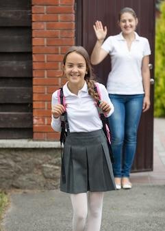 Uśmiechnięta dziewczyna wychodzi z podwórka domu do szkoły