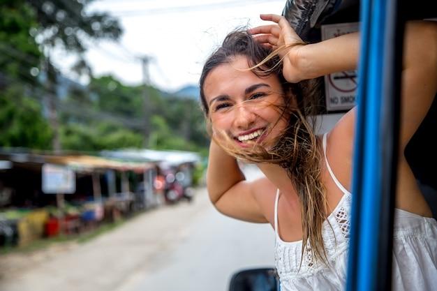 Uśmiechnięta dziewczyna wygląda przez okno taksówki, tuk-tuk