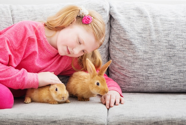 Uśmiechnięta dziewczyna z dwa królikami salowymi