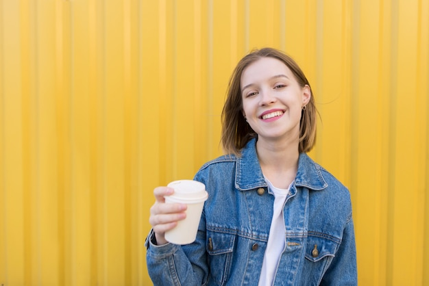 Uśmiechnięta dziewczyna z filiżanką kawy w jej rękach przeciw tłu kolor żółty ściana.