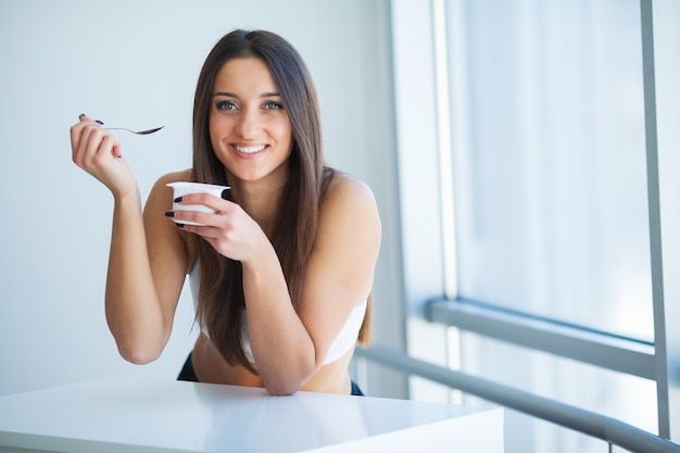 Uśmiechnięta dziewczyna z jogurtem. młoda uśmiechnięta kobieta degustacja świeżego jogurtu organicznego siedzi w białym jasnym pokoju, ubrana w biały podkoszulek.