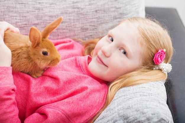 Uśmiechnięta dziewczyna z królikiem salowym