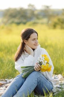 Uśmiechnięta dziewczyna z kwiatami chodzenie po lesie