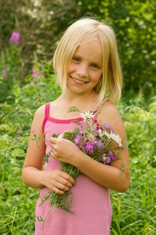 Uśmiechnięta dziewczyna z kwiatami na zewnątrz