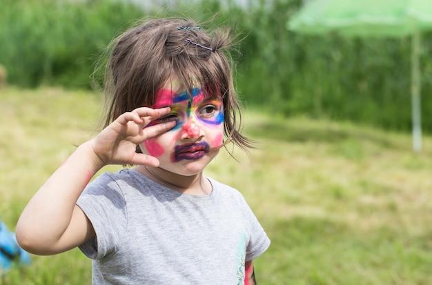 Uśmiechnięta dziewczyna z malowaniem twarzy jak tygrys, mały chłopiec malujący twarz, impreza z okazji halloween, dziecko z zabawnym malowaniem twarzy