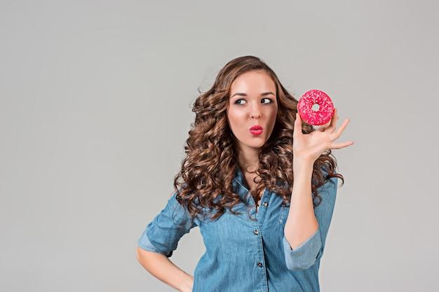 Uśmiechnięta dziewczyna z okrągłym ciastem na szarej ścianie. długie włosy.