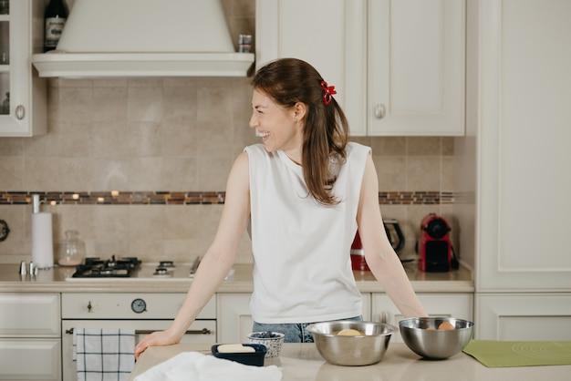 Uśmiechnięta dziewczyna z piegami i bladą skórą opiera się o stół ze składnikami na deser. młoda kobieta przygotowuje się do ugotowania w kuchni pysznej cytrynowej tarty bezowej.