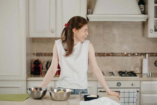Uśmiechnięta dziewczyna z piegami i bladą skórą opiera się o stół ze składnikami na deser.