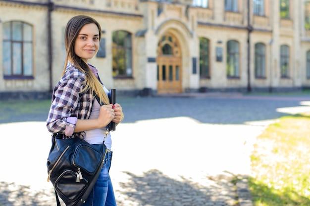 Uśmiechnięta dziewczyna z plecakiem i książką w kampusie strony