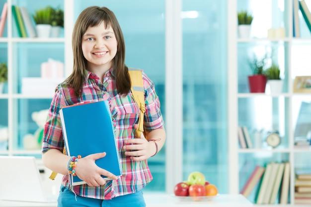 Uśmiechnięta dziewczyna z plecakiem i książki